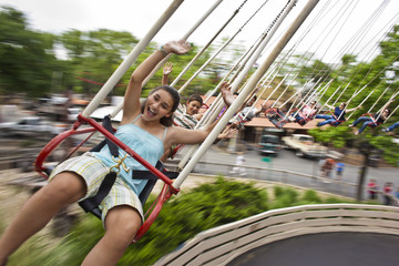Happy people on a swing ride at an amusement park.
