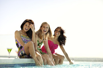 Three beautiful friends relaxing poolside.