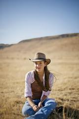 Portrait of a happy teenage girl sitting in a rural field.