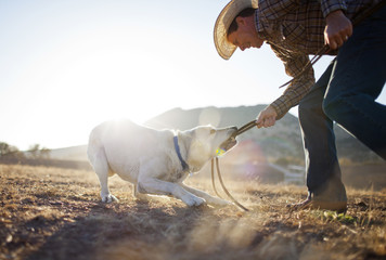 Smiling rancher playing with his dog.