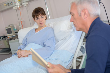 man reading to patient in hospital