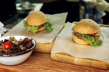 yummy burger. serving cheeseburger or hamburger with salad on wo