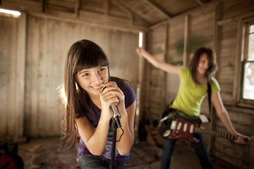 Two teenage girls having fun at band practice.