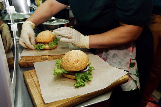 process of making burger. chef hands in gloves cooking hamburger