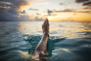 Young woman floats her leg above the water as the sun sets over the tropical ocean.