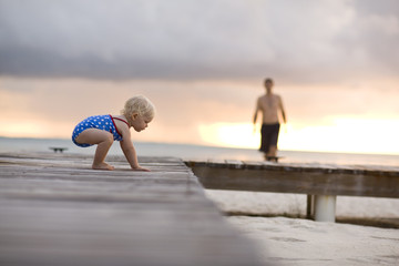Baby crawling on pier.