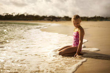 Smiling young girl in a bathing suit kneeling on sand at the edge of the water on a beach.