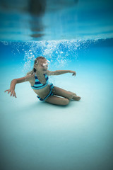 Young girl playing underwater in a swimming pool.
