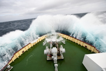 Breakers crash onto the deck of a ship on a stormy day.