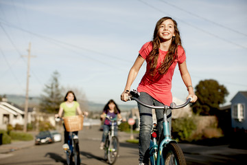 Group of teenage girls cycling along the street together.