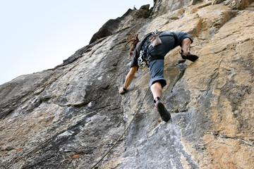 Man reaching for the next hand hold while rock climbing.