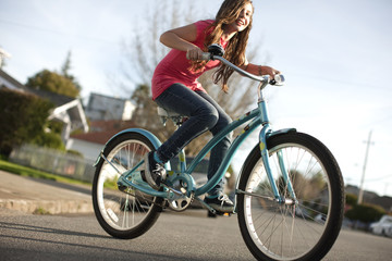 Teenage girl cycling along the street on her bike.