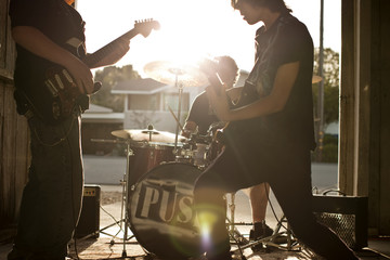 Three teenage boys playing instruments during band practice.
