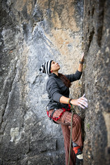 Woman reaching for the next hand hold while rock climbing.