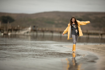 Teenage girl in gumboots and a raincoat walking along the beach.