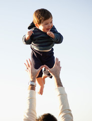 Man holds his son aloft.