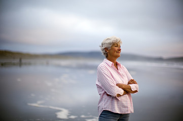 Content mature woman with her arms crossed stands on a beach and looks out at the sea.
