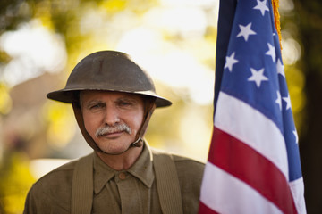 Mature male reenactor wearing an American World War steel combat helmet and uniform and holding an American flag poses for a portrait.