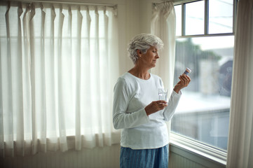 Mature woman in her pajamas holds a glass of water as she reads the instructions on a pill bottle while standing in front of a window.