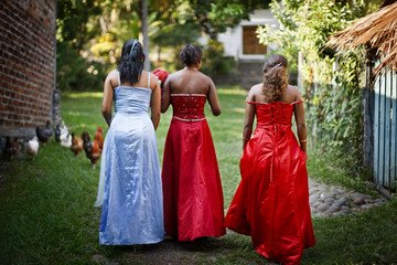 Three girls wearing prom dresses, El Salvador.