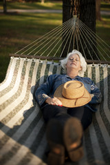 Woman relaxes by lying in hammock.