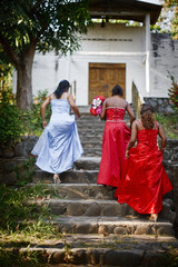 Three girls in prom dresses walking up stone steps, El Salvador.