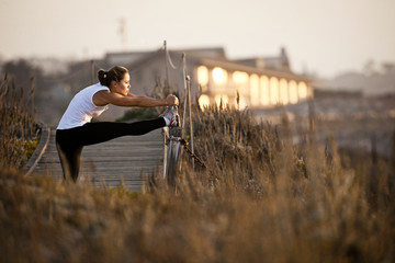 Woman stretching on boardwalk at sunset