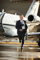 A businessman running from a plane at the airport