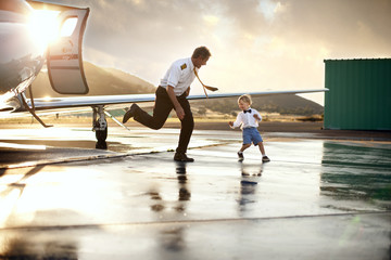 A pilot playing with a young boy at the airport