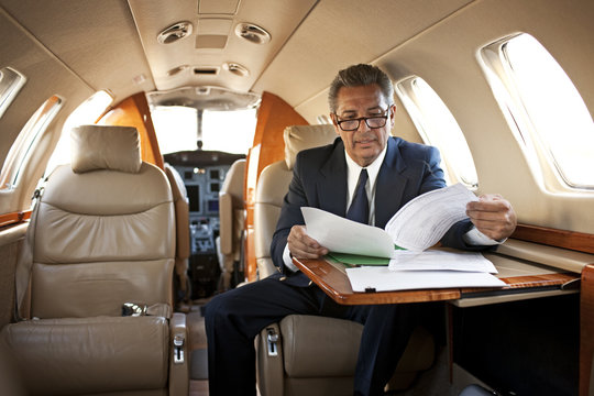 Businessman reading some documents on a private jet