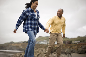 Mature man and woman holding hands at the beach