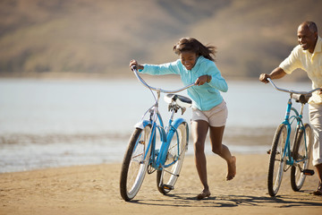 Smiling father and daughter riding their bikes on a beach.