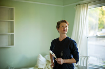Woman repainting a room in her house.