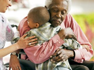 Senior man hugging his young grandson.