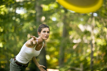 Woman throwing a frisbee in a forest.