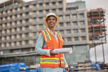 Proud young female engineer holding a roll of building plans on a construction site.