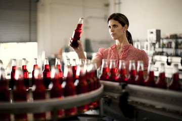 Mid adult woman examining a bottle from a production line.