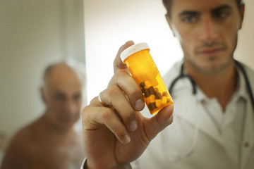Doctor holding up a bottle of pills with a worried look on his face.