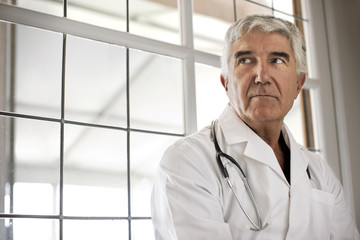 Portrait of worried looking doctor sitting in corridor.