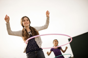 Girls playing with hula hoops.
