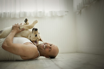 Middle aged man lying on the floor and holding his Labrador dog.