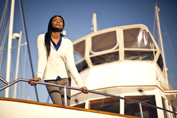 Woman on boat deck, looking at view.