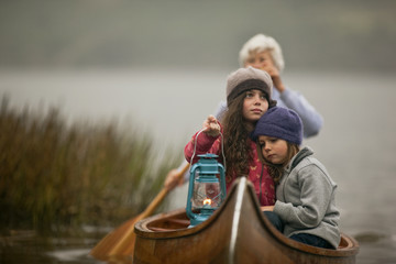 Solemn young girl holds a lit lantern and sits with her arm around her tired younger sister at the prow of a wooden canoe as a woman paddles them past reeds towards to lakeshore.