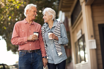 Smiling senior couple walk down the street drinking coffee and looking at each other.