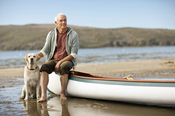 Happy senior man sitting on the edge of a canoe with his dog.