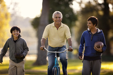 Smiling senior man having fun riding a bicycle while in a park with his two grandsons.