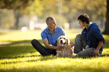 Mature man and his son having fun petting their dog together while sitting in a park.