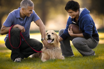 Mature man and his son having fun petting their dog together while crouching in a park.