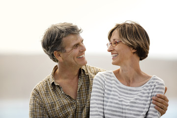 Smiling middle aged couple sitting together at a beach.
