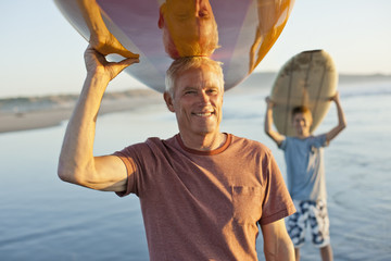 Portrait of a smiling senior man and grandson carrying surfboards on top of their heads.